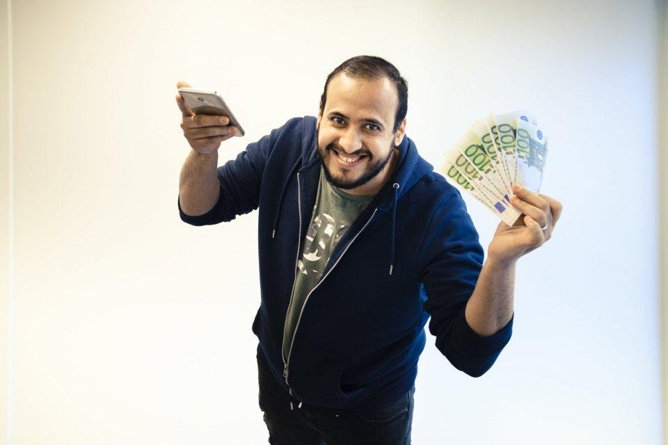 Man met smartphone en geld