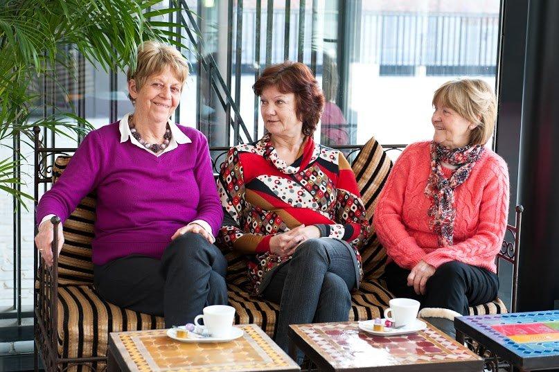 3 vrouwen die naast elkaar zitten