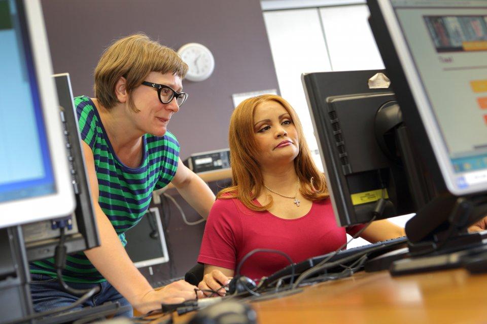Lesgeven en cursist aan de computer