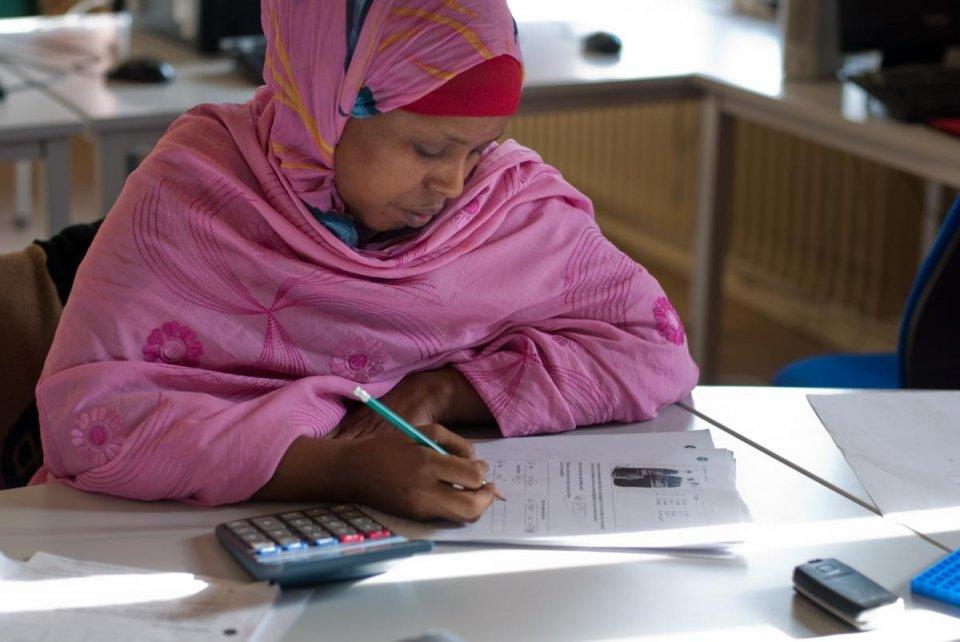 Een vrouw maakt een wiskunde oefening